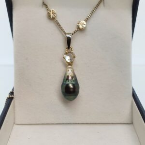 photo of a white gold chain with pendant with diamond and a black pearl.